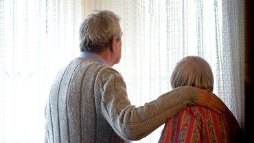 zwei Alte Menschen schauen aus Fenster