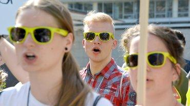 junger Mann mit grüner Sonnenbrille hinter zwei Frauen mit grüner Sonnebrille